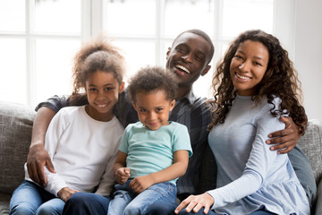 Portrait of happy large African American family at home sitting on couch together, smiling father embracing attractive wife and preschooler daughter, toddler son sitting on father knees look at camera