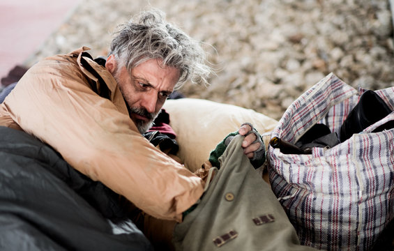 Homeless beggar man lying outdoors in city, taking something out of a bag.