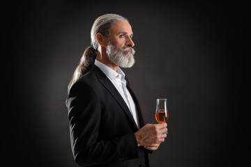 Elderly businessman with glass of whiskey on dark background