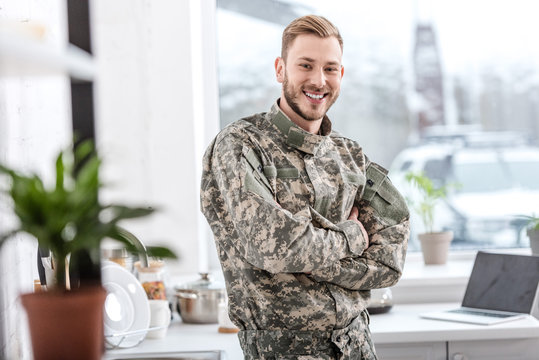handsome soldier smiling and looking at camera in kitchen