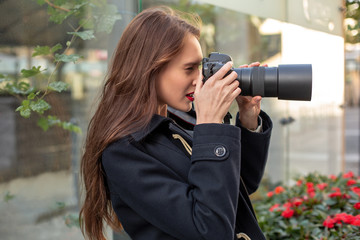 Portrait of professional female photographer on the street photographing on a camera.