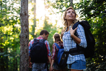 Group of young and happy people hiking in forest