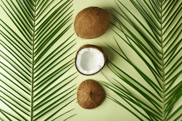 Ripe coconuts and palm leaves on color background
