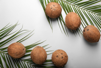 Ripe coconuts and palm leaves on light background