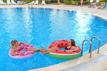 girls smiling smimming in pool on the inflatable mattress