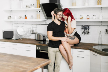 beautiful loving couple in the kitchen, beautiful redheaded girl