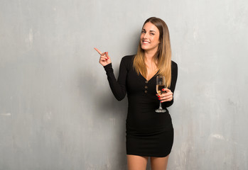 Woman with champagne celebrating new year 2019 pointing finger to the side and presenting a product