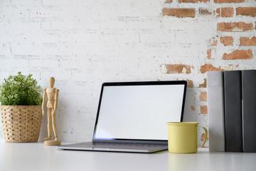 Mockup laptop showing blank screen on white desk workspace.