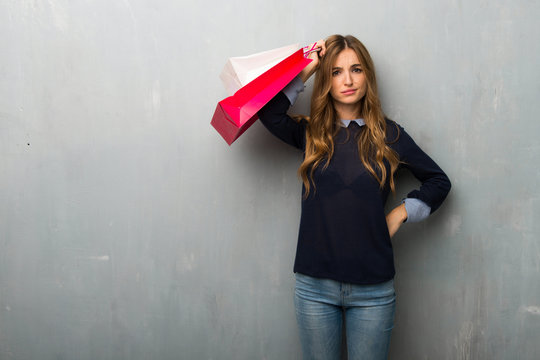 Girl with shopping bags with an expression of frustration and not understanding