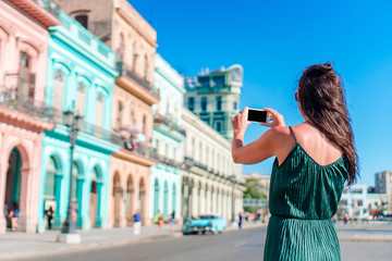 Tourist girl in popular area in Havana, Cuba. Young woman traveler smiling happy.