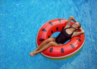 sexy girl in black bikini swimming on inflatable watermelon matt