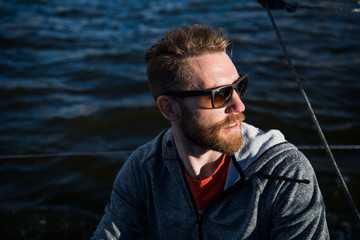 Portrait of a stylish fisher man driving a motor boat in sunset time.