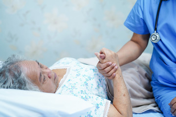 Asian nurse physiotherapist doctor care, help and support senior or elderly old lady woman patient lie down in bed at hospital ward : healthy strong medical concept.