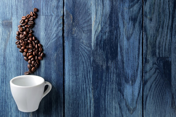 coffee cup for espresso and coffee beans in the form of smoke on a blue wooden table with space for an inscription
