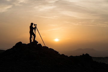 Silhouette of male landscape photographer shooting with a tripod
