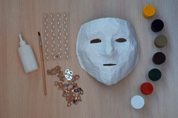 White mask of papier mache with paints and a brush for decoration