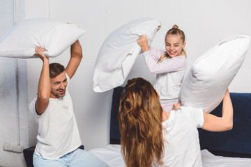 Cheerful family having pillow fight in bedroom