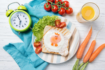 Funny toast with fried egg in a shape of chicken and alarm clock, food for kids Easter idea, top view