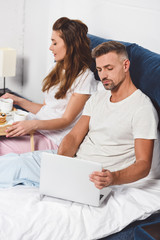 handsome husband using laptop while attractive wife having breakfast in bed