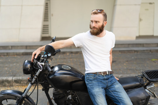 Dull biker upset about breakdown and waiting roadside assistance. Bearded young man sitting on motorcycle at parking space and looking away. Riding motorbike concept