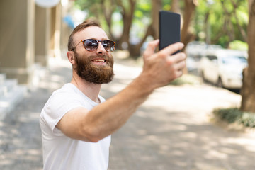 Joyful hipster guy taking selfie. Young man with bushy beard, wearing summer clothes and smiling at his phone frontal camera. Self portrait concept