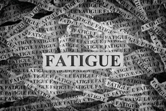 Torn pieces of paper with the word Fatigue