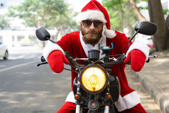 Tired Christmas courier delivering presents. Bearded young man in Santa costume sitting on parked motorcycle and looking at camera through sunglasses. Christmas order delivery concept