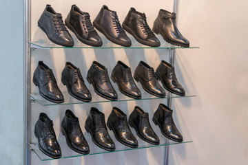 Men's leather shoes on the shelf in the store. Racks in the store of clothes and accessories. Shelves with stylish men's shoes. Many classic shoes and boots.