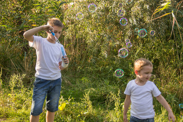 The boy inflates soap bubbles in nature