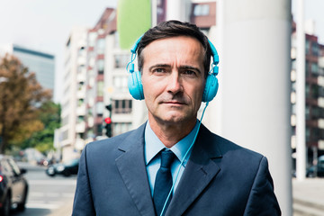 Portrait of businessman with headphones in the city