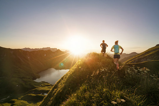 Man and woman running on mountain trail during sunrise