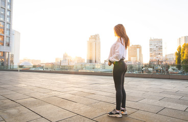 Sports girl with a beautiful bottom stands on the background of the city at sunset. Sports concept.