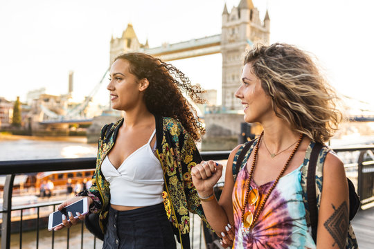 UK, London, two friends together in the city with Tower Bridge in background at sunset