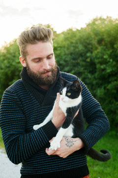 Young man holding a cat in Sweden