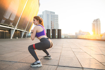 Girl with an appetizing ass squat. Sexy girl with a nice ass deals with squats on the background of the sunset. Girl doing sports against the background of the city at sunset.
