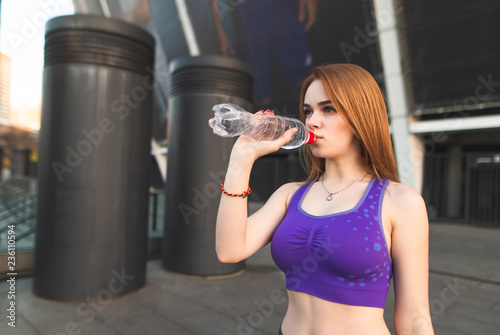2b91adcf Portrait of a sports girl dressed in the top, drinking water from the  bottle and looking to the side.Girl wearing sportswear is trained on the  street and ...