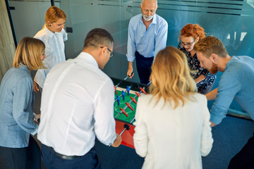 Colleagues playing foosball in office