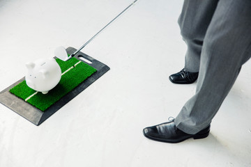 Close-up of businessman playing golf with piggy bank