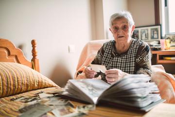 Portrait of senior woman adding old photos to a photo album at home