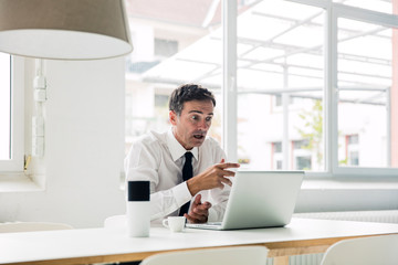 Shocked businessman looking at laptop on table in office