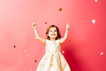 Studio shot of toddler girl throwing confetti Wall mural