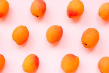 Fresh apricot on pink background. Flat lay, closeup. Modern summer pattern.