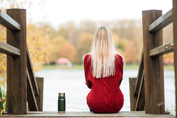 beautiful happy girl in a red sweater with a thermos outdoors, a woman is resting in nature