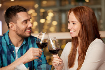 celebration, holidays and people concept - happy couple drinking red wine at restaurant