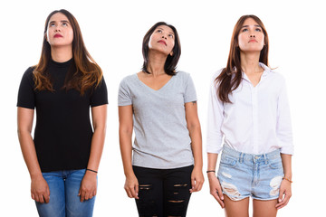 Studio shot of three young Asian woman friends looking up