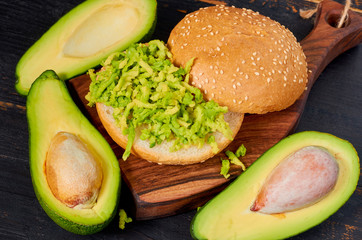 Healthy avocado burger on the wooden board - traditional Mexican dish. Vegetarian green sandwich on the black kitchen background. Close up view