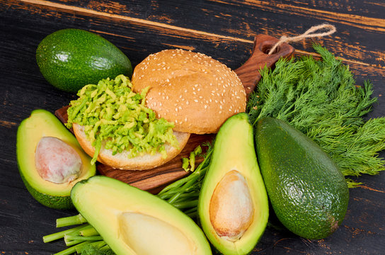 Veggie avocado sandwich with dill on the wooden board. Traditional healthy Mexican dish - diet green guacamole burger on the black kitchen background. Side view