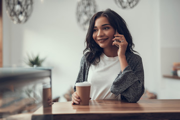 Peaceful relaxed young lady smiling and holding her carton cup of coffee while having a pleasant phone talk in a cafe