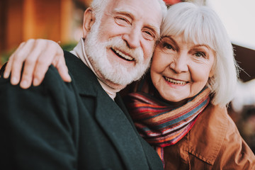 Close up portrait of happy senior lady hugging her joyful husband. They looking at camera and smiling