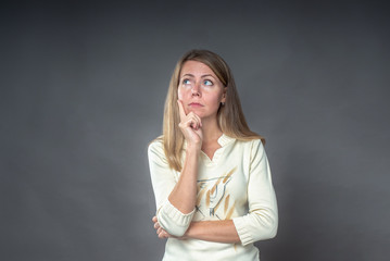 Thoughtful woman looks aside with pensive expression, plans something with many questions in her head. Puzzled female holding hand near the face, looking seriously up, standing near grey background